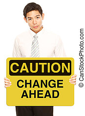 Caution: Change Ahead - A man holding a conceptual business...