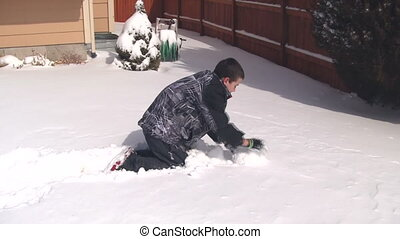 Boy making large snowball for snowman