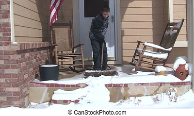 Boy sweeping snow off porch - Boy sweeping the snow off of a...