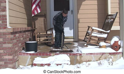 Boy sweeping snow off of porch