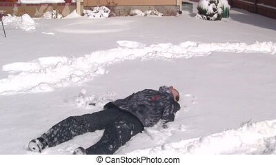 Boy making snow angel