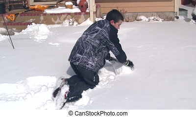 Boy making large snowball to make snowman