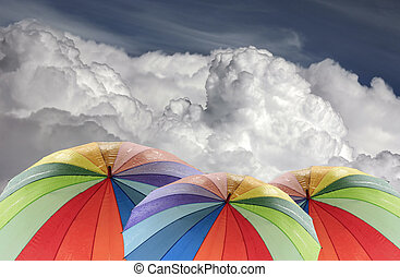 Rainbow umbrella on a background of the cloudy sky
