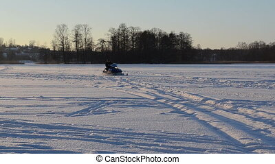 snowmobile man lake snow - man with helmet and goggle drive...