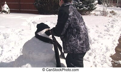 Boy putting face on snowman