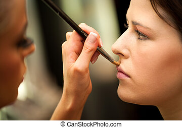 Macro close up of hand at make up session.