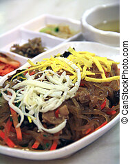 Japchae, Korean glass noodles with side dishes in the background