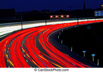 cars on freeway at night - many cars are driving at night on...
