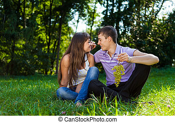 Young happy couple flirting in a summer sunny park