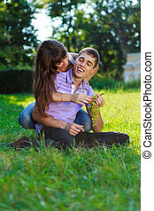 Happy cheerful couple fooling around in a summer sunny park
