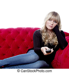 young blond haired girl on red sofa with remote control in...