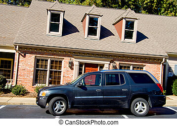Leaning Apartments - An SUV parked in fron of a leaning...