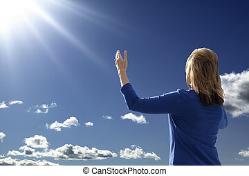 Outdoors Worship - Young lady raising her arms in worship...