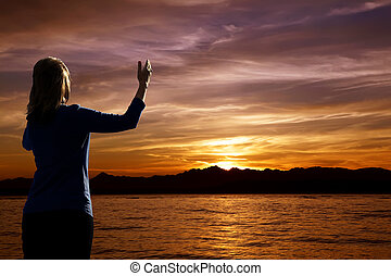 Sunset Worship - Young woman with arms raised in praise...