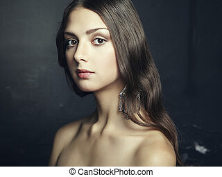 Portrait of beautiful young woman with earring Fashion photo...
