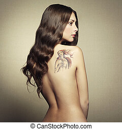 Portrait nude young woman with tattoo. Fashion photo
