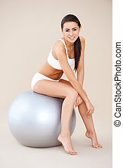 Brunette shapely woman resting on fitness ball and smiling