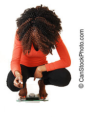 Girl crouching on scale. - A lovely black teen girl...