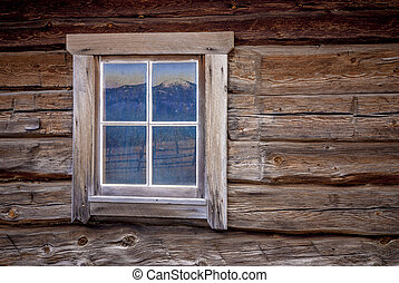 Log cabin window with mountain reflection