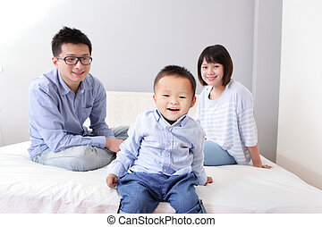 A happy family sitting on white bed - cute boy sitting on...