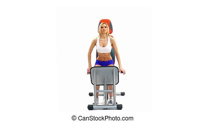 Sporty woman doing exercises on hydraulic trainer, on white...
