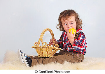 Boy eating yellow aplle.