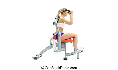 Slender woman training on isodynamic exerciser, on white...