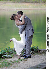 bride and groom are kissing on the shores of a mountain lake
