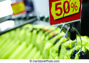 Sport and casual clothes on hangers in the shop - Clothes on...