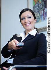 woman and zapping - businesswoman, to make use of remote...