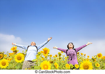relaxed senior couple standing in the sunflower garden