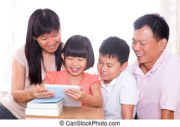 Parents and children using tablet pc together - Asian family...