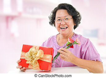 Happy mothers day concept Asian senior mother showing a gift...