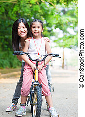 Asian family riding bike - Asian parent and child riding a...