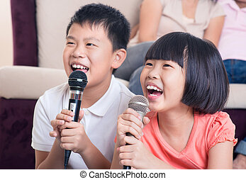 Family at home. Portrait of a happy Asian children singing...
