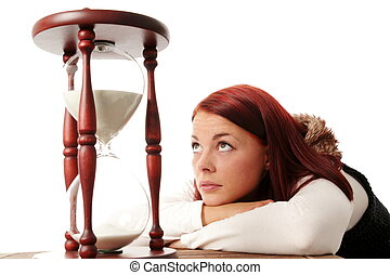 Young woman looking up to a big hourglass