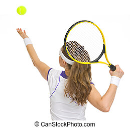 Tennis player serving ball rear view