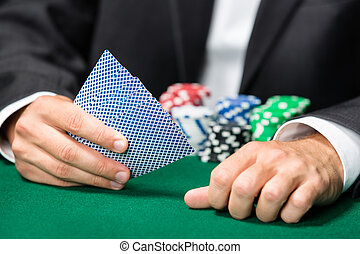 Gambler playing cards with poker chips on the table