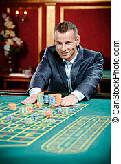 Gambler stakes playing roulette at the casino table