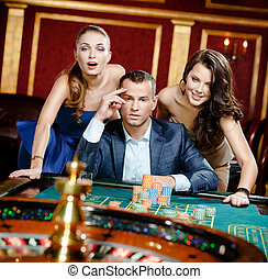 Man with two girls playing roulette at the casino club