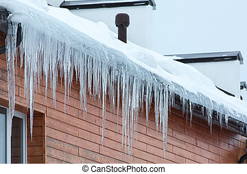 Winter hanging icicles on the house roof