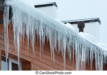 Roof of the house with snow and icicles overhanging