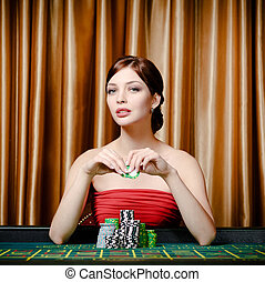 Female gambler sitting at the casino table - Portrait of...
