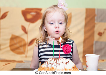 Little Caucasian girl blowing candles on birthday cake