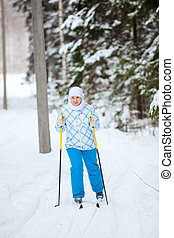 Happy Caucasian woman skiing in wintry forest alone