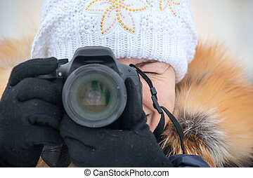 Close up female photographer with camera outdoor in winter...