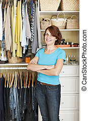 Smiling woman near closet - Happy woman standing in front of...