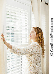 Smiling woman looking out window - Happy woman looking out...