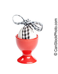Easter egg with checked ribbon is in egg cup