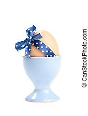 Colored easter egg with blue polka-dotted ribbon in blue egg...